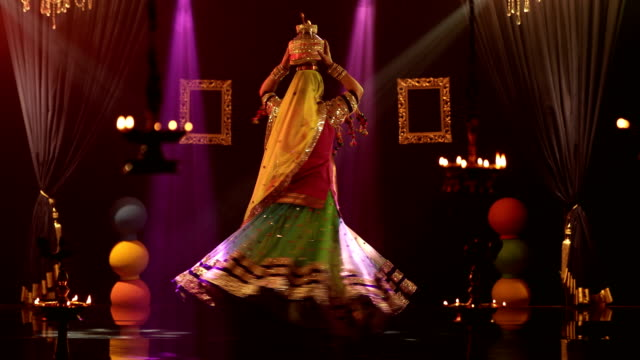 ms woman balancing burning pot on her head while performing traditional ghoomar dance on stage/ india - カーテン止め点の映像素材/bロール