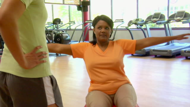 MS Woman balancing on exercise ball with her arms out as she talks to her personal trainer/ San Antonio, Texas