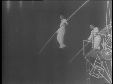 Woman balancing on rods carried by two men during acrobatic act / Betty Sinkovich and Ray Billetti posing with their wedding party / Sinkovich and...