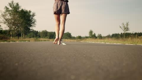 stockvideo's en b-roll-footage met woman balancing over street - barefoot