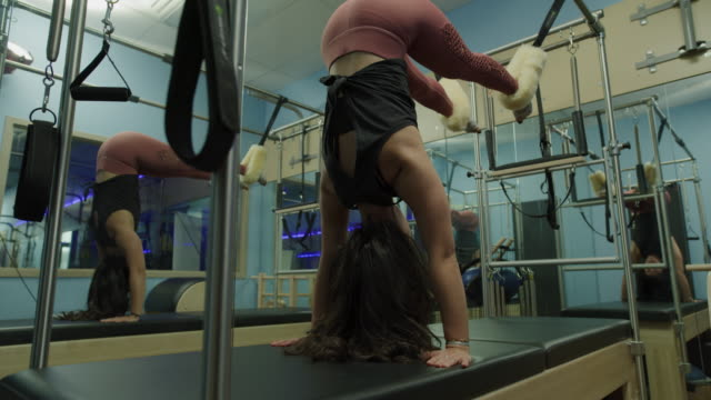 woman balancing upside-down with feet in straps on pilates reformer exercise machine / lehi, utah, united states - lehi stock videos & royalty-free footage