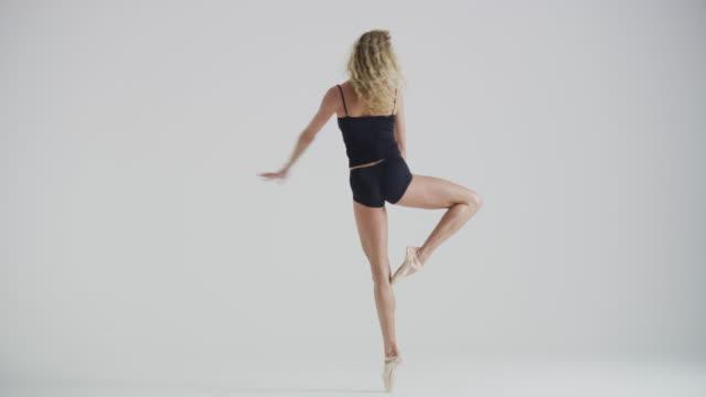 vídeos y material grabado en eventos de stock de woman ballet dancer dancing, practicing, and warming up in studio - de puntas
