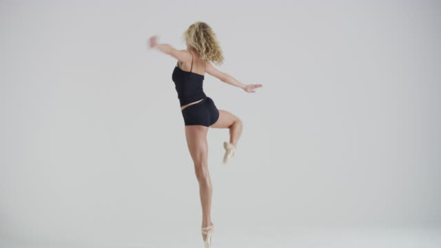 vidéos et rushes de woman ballet dancer dancing, practicing, and warming up in studio - souplesse