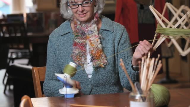 ms pan tu woman balling yarn off spooler in knitting store / richmond, virginia, usa - トルソー点の映像素材/bロール