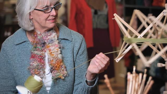 ms pan td woman balling yarn off spooler in knitting store / richmond, virginia, usa - トルソー点の映像素材/bロール