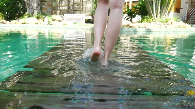 Woman barefoot walk in the water