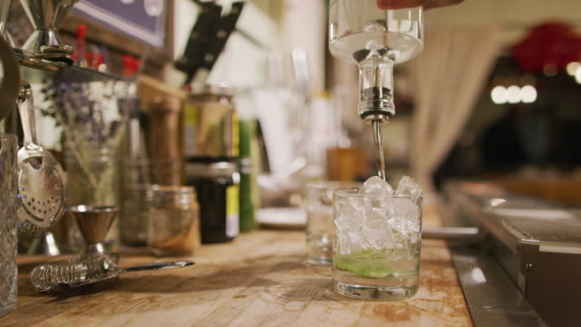 a woman bartender prepares a mixed drink mojito at a bar (with muddled mint, ice, and rum) - bartender stock videos & royalty-free footage