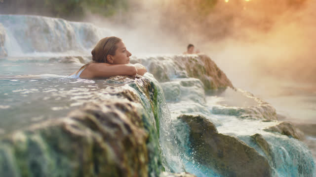 vidéos et rushes de slo mo femme se baigner aux sources chaudes de saturnia au coucher du soleil - source naturelle