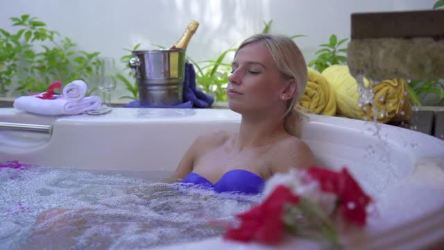 a woman bathing in a spa hot tub whirlpool bathtub hot tub. - slow motion - hot tub stock videos and b-roll footage