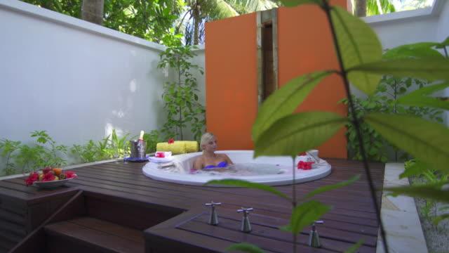 A woman bathing in a spa hot tub whirlpool bathtub hot tub.