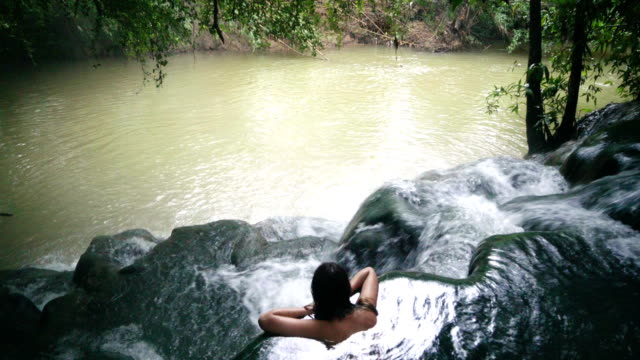 Woman bathing in hot spring waterfall