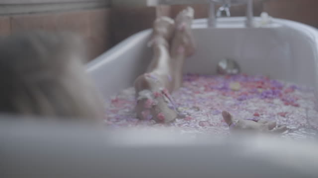 a woman bathing, taking a bath in a bathtub at a resort hotel spa bathroom with flowers petals. - taking a bath stock videos & royalty-free footage