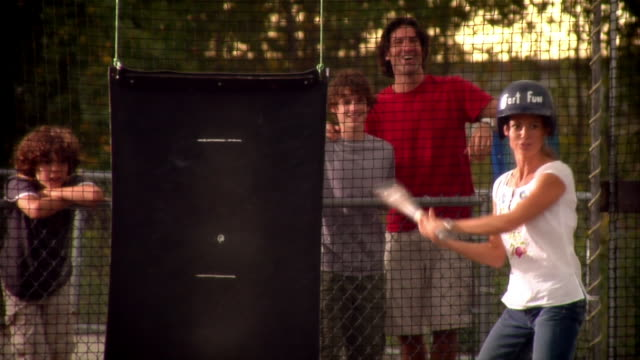 stockvideo's en b-roll-footage met woman batting in batting cage as family watches and cheers her on - westers schrift