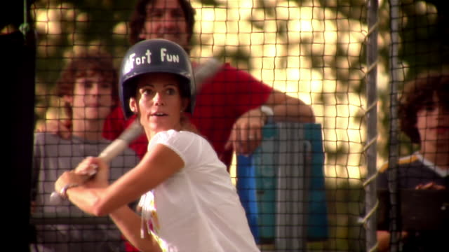 woman batting in batting cage as family watches outside cage and cheers her on - scrittura occidentale video stock e b–roll