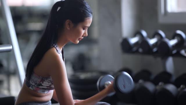Vrouw begint gewicht opleiding in de sportschool