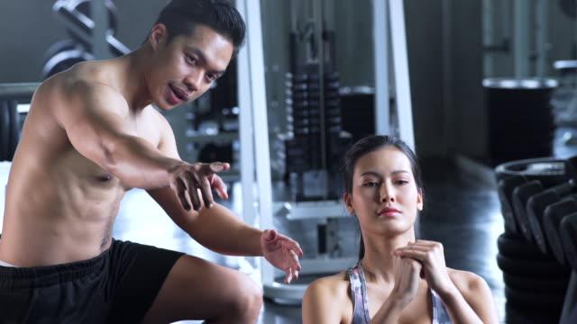 Vrouw begint gewicht opleiding met trainer in de sportschool