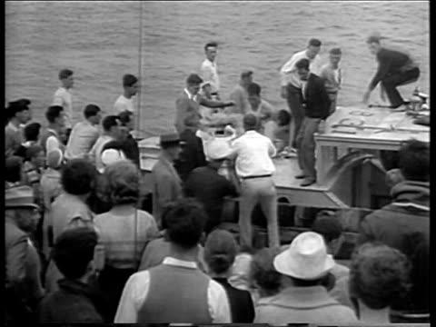 vídeos y material grabado en eventos de stock de woman being carried from rescue boat after morro castle ship fire / crowd of onlookers / man carrying survivors from rescue boat thru crowd / crowd... - 1934
