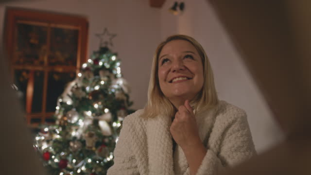 ms woman being ecstatic after opening her christmas present - low lighting stock videos & royalty-free footage