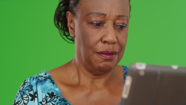 woman being frustrated as she uses her tablet on green screen - maestra video stock e b–roll