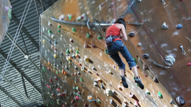 woman being lowered from an indoor climbing wall - kletterwand kletterausrüstung stock-videos und b-roll-filmmaterial