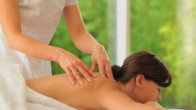 woman being massaged in a spa center - massage table stock videos & royalty-free footage