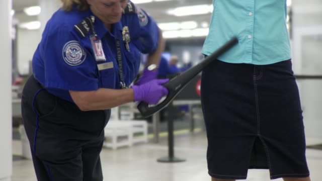 vídeos y material grabado en eventos de stock de ms woman being swiped with metal detector at airport / jacksonville, florida, usa  - seguridad
