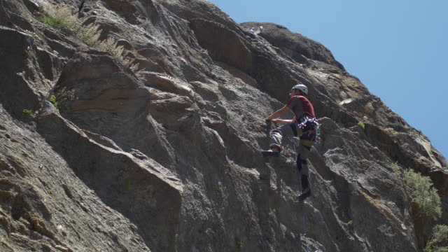 a woman belaying a man while rock climbing. - belaying stock videos & royalty-free footage
