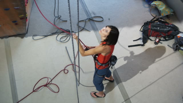 woman belaying another climber on an indoor climbing wall - belaying stock videos & royalty-free footage