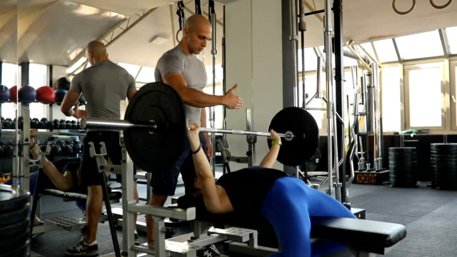Woman bench press exercise with fitness trainer
