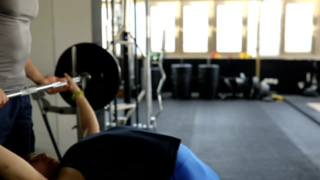 Woman bench press exercise with personal trainer