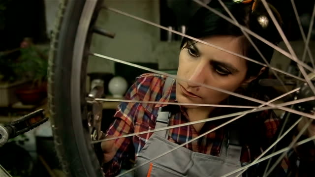 woman bicycle mechanic repairing wheel on bike in a workshop - repairing stock videos and b-roll footage