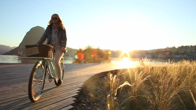 Woman bicycles along lakeshore pathway in autumn