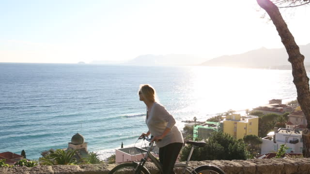 Woman bikes along rural road above coastal village, looks out to sea