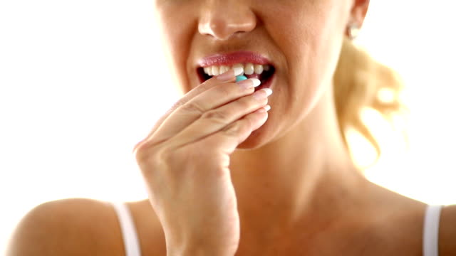 Woman biting a pill