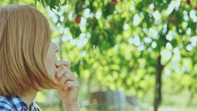 新鮮な桃ジュースの収穫、スローモーションをかむ女性 - モモ点の映像素材/bロール