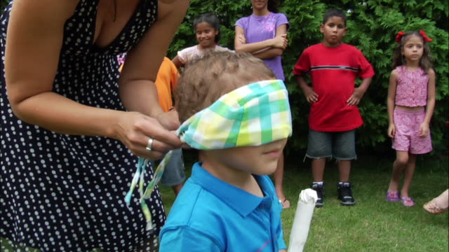 vídeos y material grabado en eventos de stock de woman blindfolding young boy who holds stick and stands underneath pinata / people watching in background / new jersey - papier