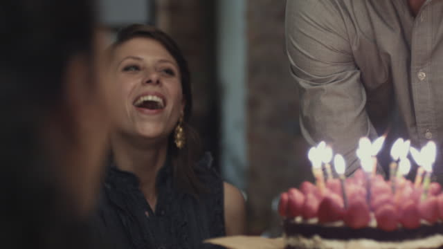 cu ms slo mo woman blowing birthday cake, friends applauding and toasting wine / new york city, new york, usa - candle stock videos and b-roll footage