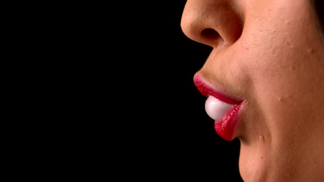 Woman blowing bubble gum close up
