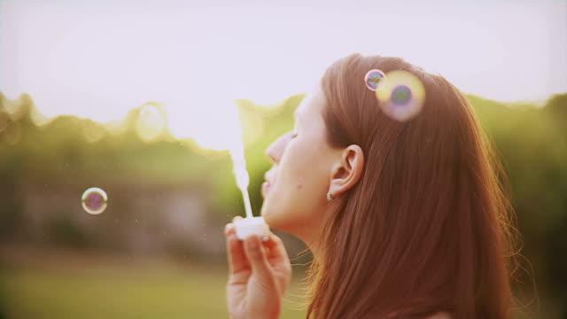 vídeos y material grabado en eventos de stock de mujer soplando burbujas de aire libre - sólo mujeres jóvenes