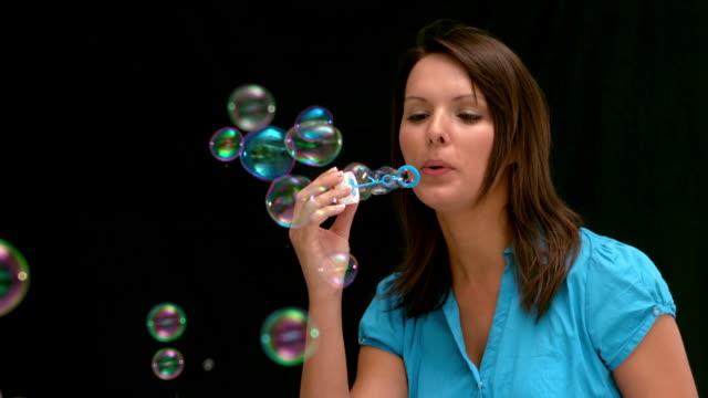 woman blowing bubbles - mittellanges haar stock-videos und b-roll-filmmaterial
