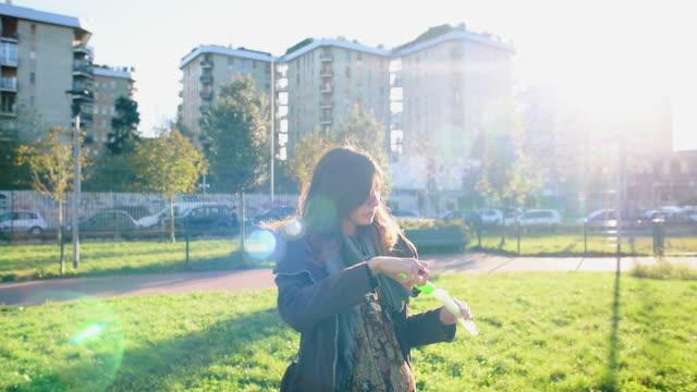woman blowing bubbles - cappotto invernale video stock e b–roll