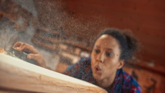 slo mo woman blowing dust off a piece of wood she just sanded - passion stock videos & royalty-free footage