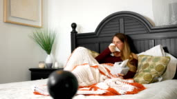 Woman blowing her nose with box of tissues sick in bed ALT