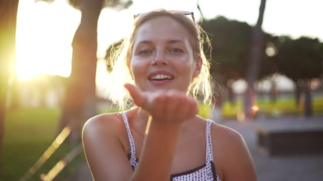 Woman blowing kisses in a park. Summer relaxation