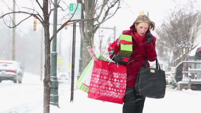 ws pan woman blowing nose in snow, holding christmas presents on city street / richmond, virginia, united states - tragetasche oder tragebeutel stock-videos und b-roll-filmmaterial