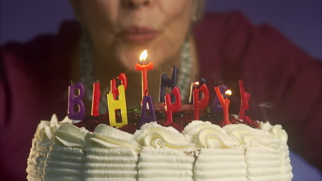 woman blowing out the candles on a birthday cake, sweden. - birthday candle stock videos & royalty-free footage