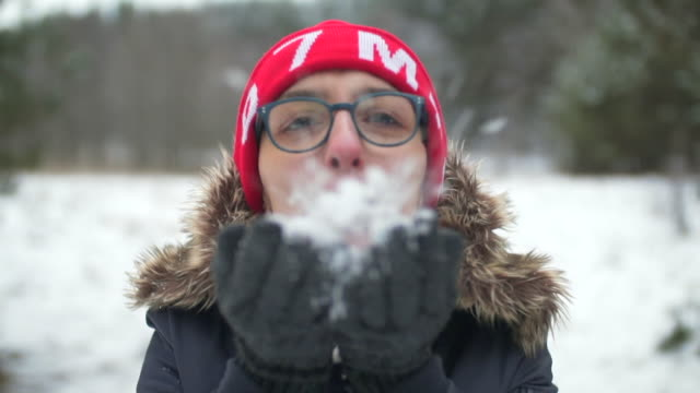 woman blowing snowflakes in winter landscape - stazione sciistica video stock e b–roll