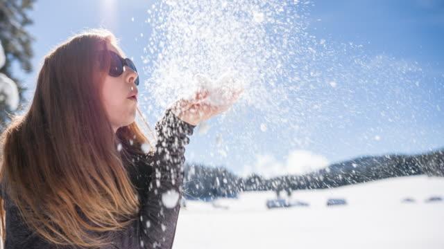 vídeos y material grabado en eventos de stock de mujer soplando copos de nieve en paisaje de invierno - soplar