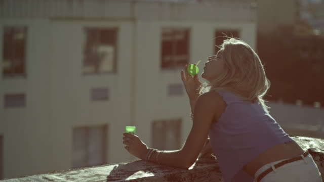 woman blowing soap bubbles - balcony stock videos & royalty-free footage