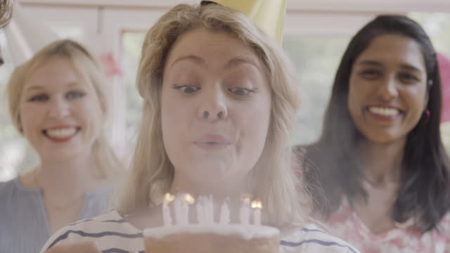 vidéos et rushes de woman blows out candles of birthday cake while friends are cheering and laughing. - anniversaire